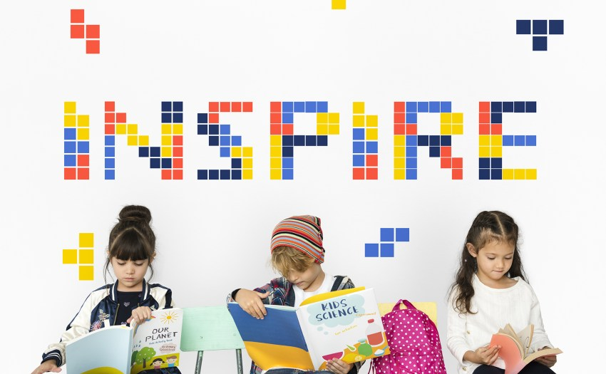 palabra INSPIRE escrita en bloques en la pared sobre tres ninos sentados