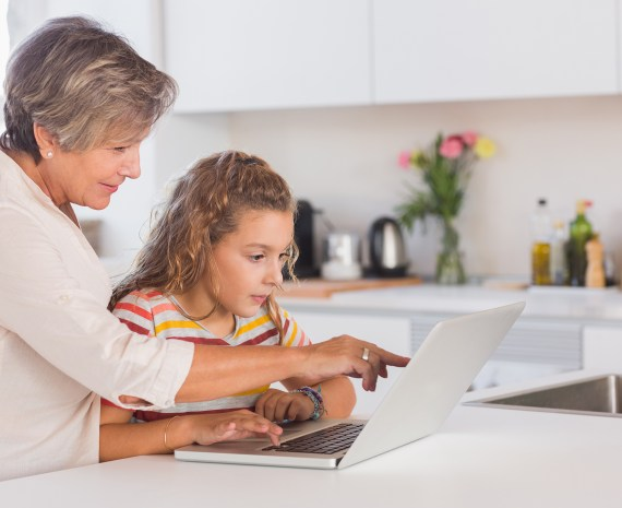 una abuela señalando la pantalla de una laptop a su nieta - life long learning