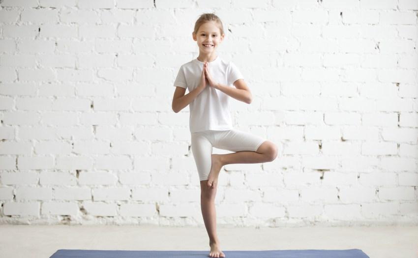 niña en postura de arbol vestida de blanco - 5 posturas de yoga