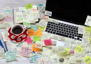 un escritorio desorganizado y lleno de post it - organizado
