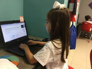 niña con postura correcta para manejo de teclado