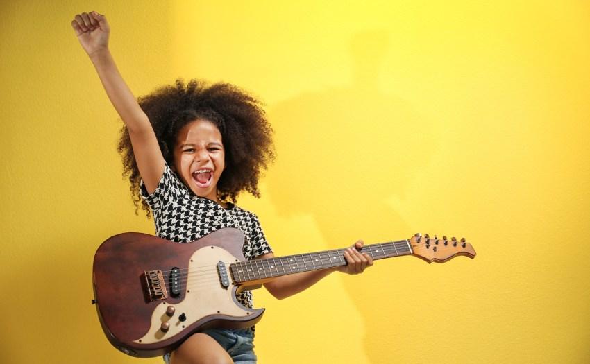 Una estudiante con una guitarra eléctrica y una mano en el aire - música y el aprendizaje