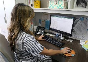 Una mujer sentada frente a un monitor preparando un presupuesto