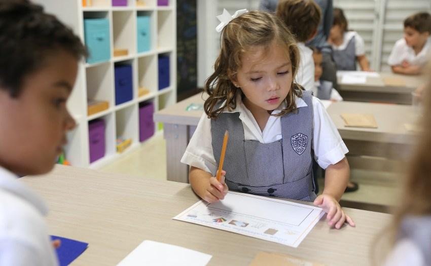 Niña de preescolar con un lápiz y papel en un makerspace