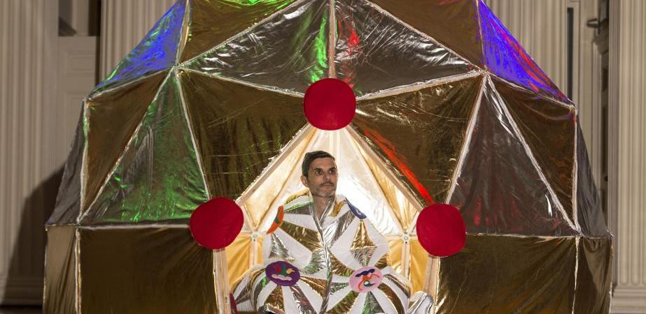 Athens-based artist Angelo Plessas sits in his gold and silver tent , part of the art exhibition