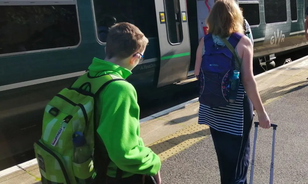 A family board a train with bags packed for a long journey