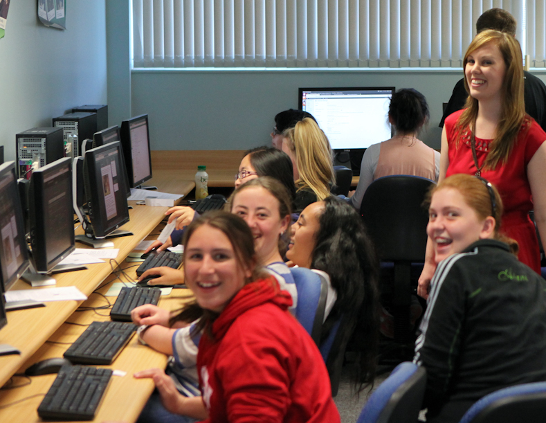 A room full of young women sitting at computers and smiling.