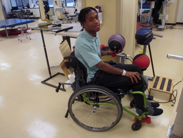 Semaj Clark in physical therapy gym, balancing ball in hand.