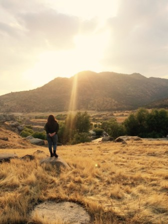 Monserrat Zarza standing in dry grasses and watching sunset behind hills.