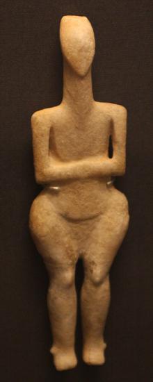 Figurka przedstawiająca kobietę, utrzymana w stylu naturalistycznym (kultura Grotta-Pelos, ok. 3000-2800 BC). Opracowanie głowy przypomina późniejsze idole, mimo braku zaznaczonego nosa, natomiast ciało - z wyraźnie zaznaczonymi biodrami - jest typowe dla tej odmiany. Wyjątkowe jest opracowanie zagłębień oddzielających ramiona od ciała. British Museum, Londyn.