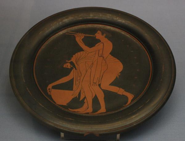 Talerz z ok. 520-510, Ateny, z przedstawieniem dwóch mężczyzn. Zwraca uwagę kompozycja kontrastująca ze sobą zamknięcie postaci pochylonego starszego mężczyzny i otwarcie postaci grającego na flecie, wyprostowanego młodzieńca.