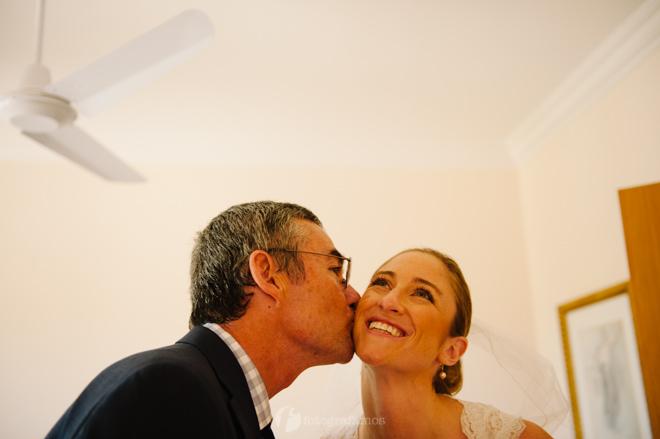 portrait of father kissing bride