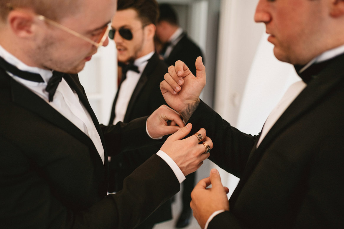 groomsman helping tattooed groom get ready at casa rupi wedding