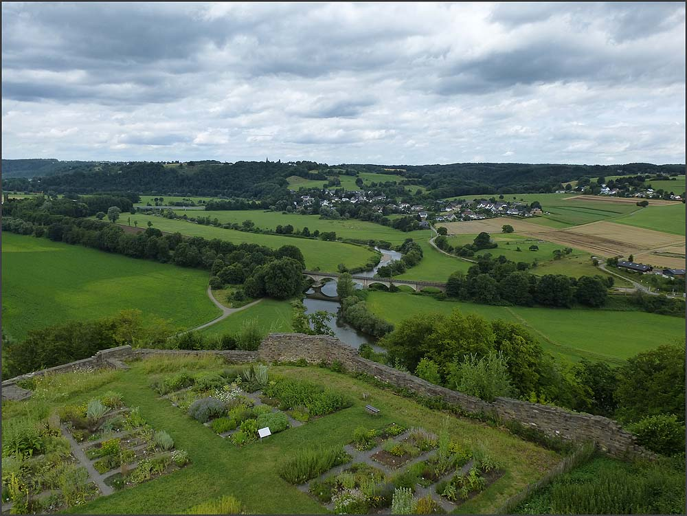 Ein herrlicher Blick von der Terasse oben auf der Burgruine auf den Kräutergarten und dahinter das Siegtal
