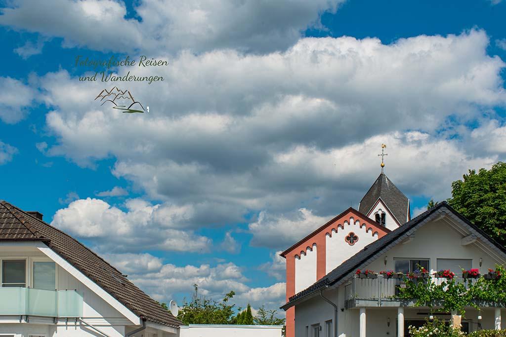 Hinter den Häusern schaut vorwitzig die Kirche von Frücht hervor