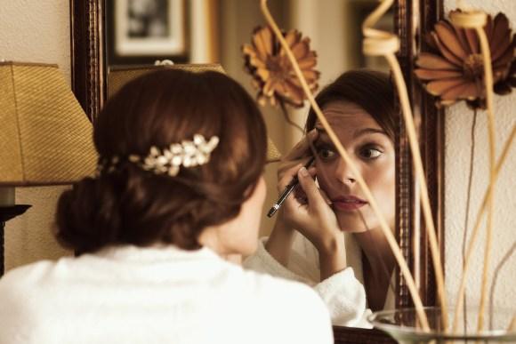 Novia dándose los últimos toques de maquillaje enfrente del espejo.