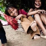 En las afueras de la capital de Camboya, Phnom Penh, existe un barrio llamado Andong, creado poco a poco por personas que el gobierno desaloja cuando el mercado inmobiliario lo requiere. Estas personas llegan aquí, donde un montón de ONGs se han asentado entre chabolas para intentar dar un poco de dignidad a sus vidas. En Camboya es fácil desalojar, el gobierno lleva haciéndolo durante décadas, desde que los Jemeres Rojos quemaran la mayoría de contratos de propiedad privada que tenía la población. Ahora poca gente posee una casa de manera legal en Camboya. Los caminos son de tierra y muchos estaban inundados. Las casas son simples chabolas de madera con una hamaca en su interior, donde toda la familia duerme en el suelo. Aún así sólo vimos sonrisas y alegría, como en esta foto donde varias niñas juegan con un columpio improvisado con una hamaca.