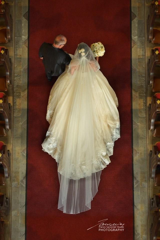 La sposa procede lentamente verso l'altare. L'accompagna il babbo. Tutti gli occhi sono puntati su di lei. #fotografomatrimoni #bridedress