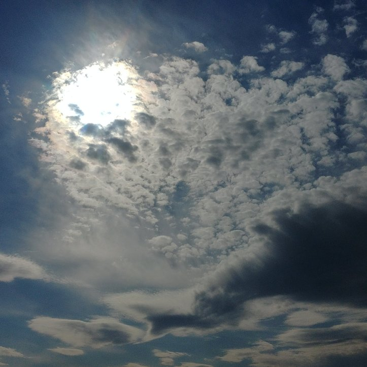 Funny clouds and sun in blue sky, nature photo by fotosbykarin