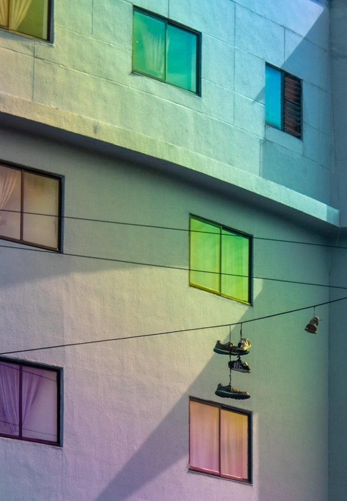 zapatillas colgando en cables y al fondo ventanas de colores