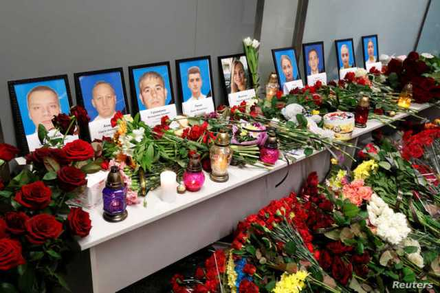 Flowers and candles are placed in front of the portraits of the flight crew members of the Ukraine International Airlines…