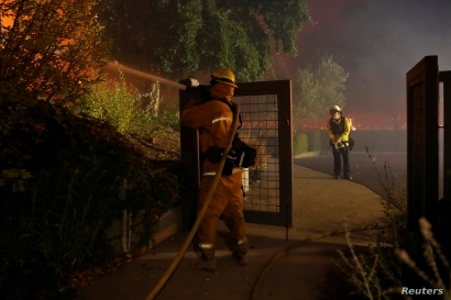 A firefighter hoses a hot spot while battling the Kincade Fire in Geyserville, Calif., Oct. 24, 2019.