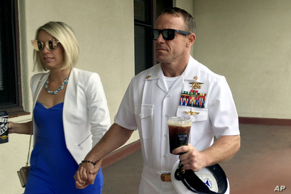 FILE - Navy SEAL Edward (Eddie) Gallagher, right, walks with his wife, Andrea Gallagher, as they arrive at a military court on Naval Base San Diego, in San Diego, California, June 26, 2019.