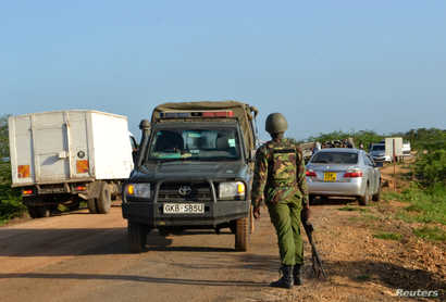 A Kenyan police officer observes motor vehicle traffic near the scene where armed assailants killed three people and injured…