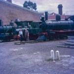 Two men standing by a Steam Engine