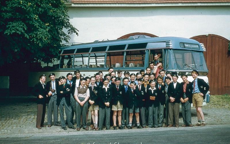 Schoolboys posing by a coach