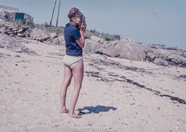Girl on beach taking photo