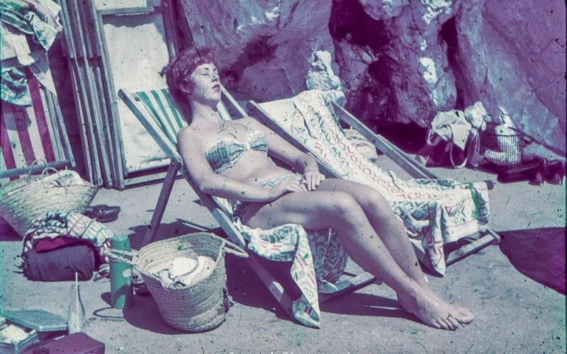 Woman sunbathing in a deckchair on a beach