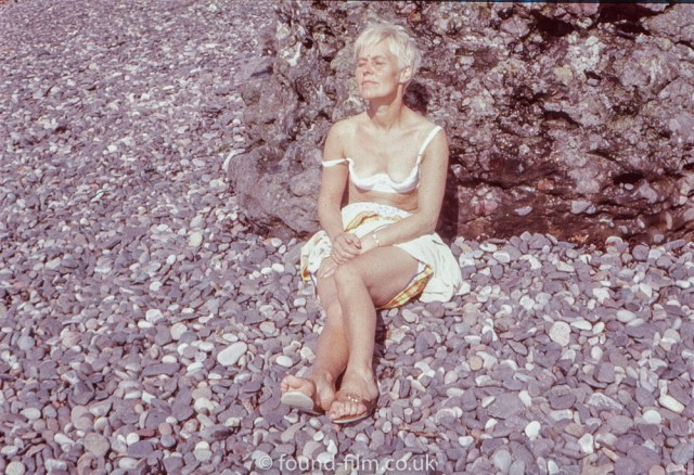 Photo of a lady sunbathing on a beach during a holiday