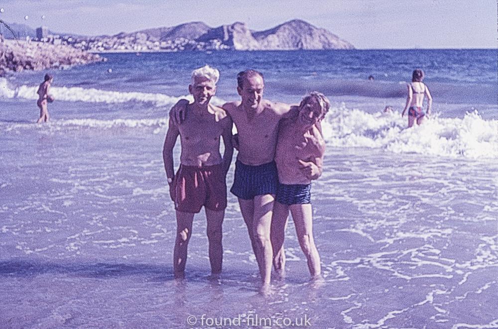 Three men in the sea on a beach