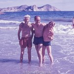 Three men standing in the sea on a beach