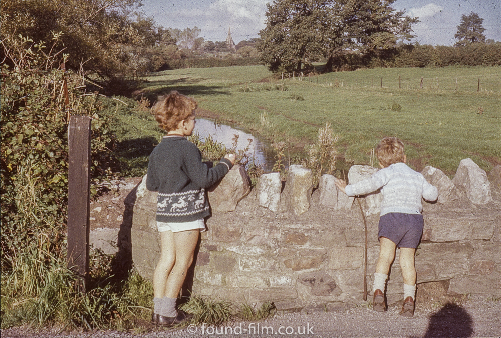 Two children by stone wall