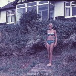 Girl in a bikini in front of a house
