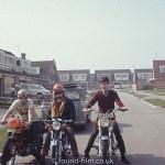 Men sitting on motorbikes in a housing estate, August 1972
