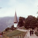 A couple walking along path towards a church in the mountains