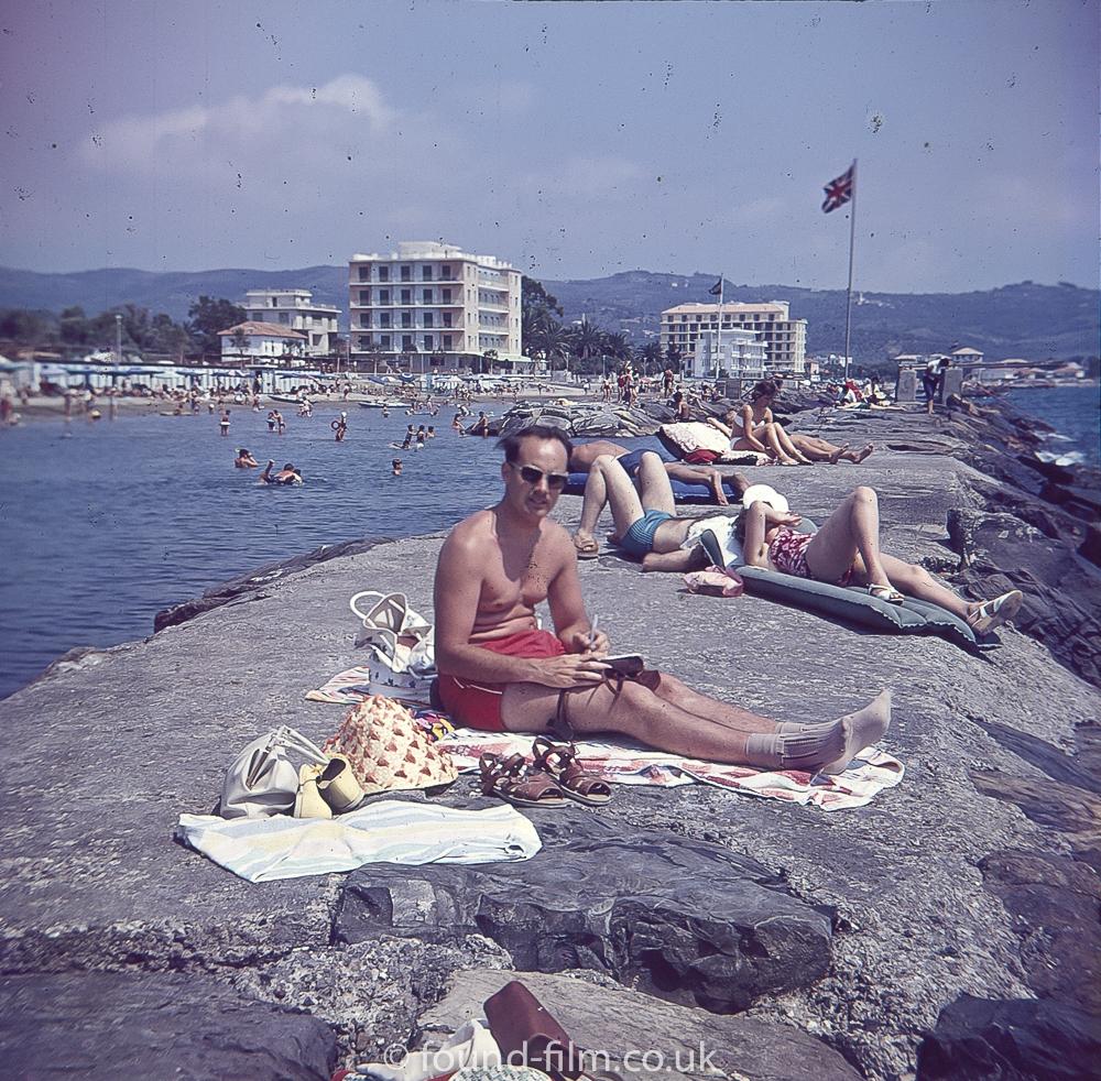 Man sunbathing and writing on Rocks