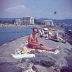 Man sunbathing and writing on Rocks early 1960s