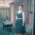 Woman posing in back yard in the 1950s