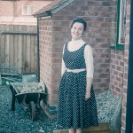 Woman posing in back yard in the 1950s