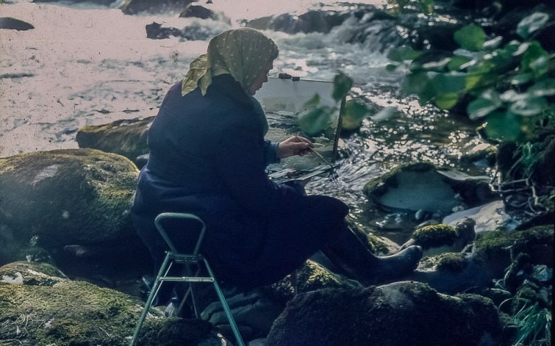 Artist sitting by a river with her Easel