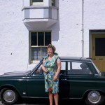 A Kodachrome slide of a woman standing next to a dark green ford car in Ullapool, August 1967