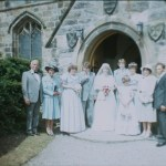 A colour slide of a wedding group by the church door