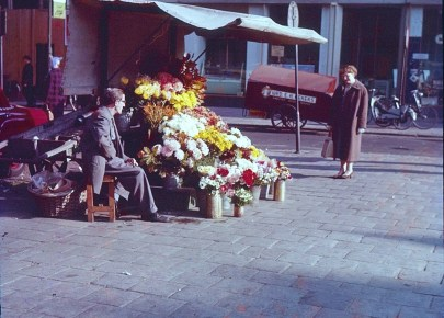 A woman looking at flowers from a street sellers stall