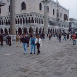 A photo of people walking in Venice with Doge's palace in the background