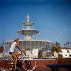 A girl on a bike in front of a fountain