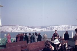 Tourists on a boat by white cliffs